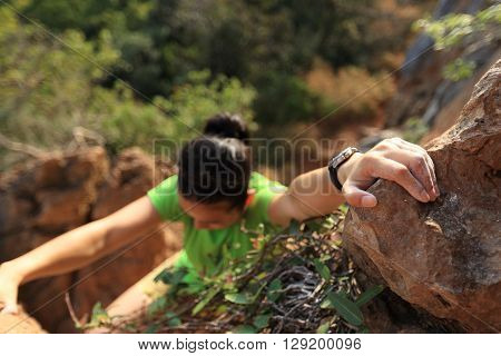 young woman rock climber climbing on mountain cliff