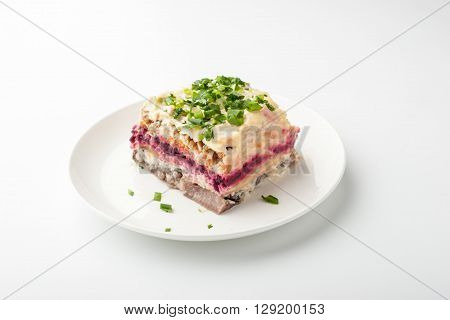 Herring under beetroot and mayonnaise in a white ceramic plate horizontal