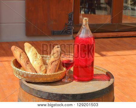 The picture shows a wicker basket with bread. Next set glass bottle of red wine which is located near a glass filled with wine.