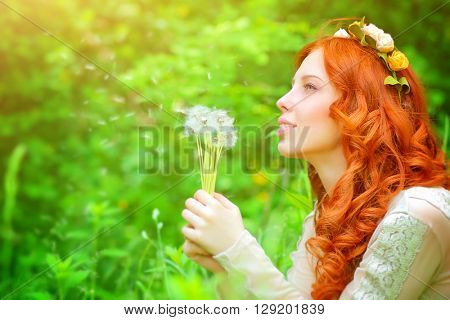 Portrait of a beautiful girl wearing floral wreath, enjoying spring grass field, holding in hands bouquet of a dandelion flowers and daydreaming about a wish