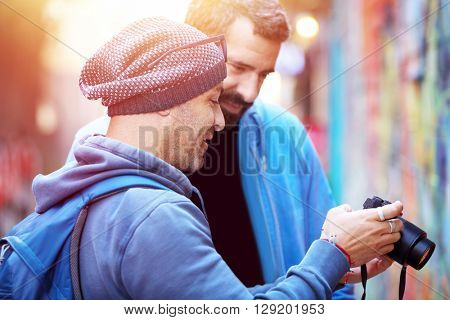 Two happy friends outdoors, conversing and looking at the images on the photo camera, best friends enjoying active summer vacation