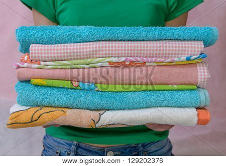 Woman holding folded clothes in hands. Closeup