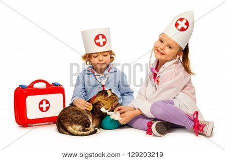 5 years old children dressed at whites and doctor cap bandage paw to a cat