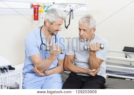 Physiotherapist Assisting Senior Man In Lifting Dumbbells