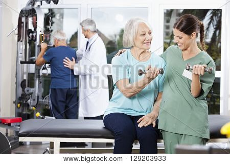 Nurse Guiding Senior Woman Exercising With Dumbbell