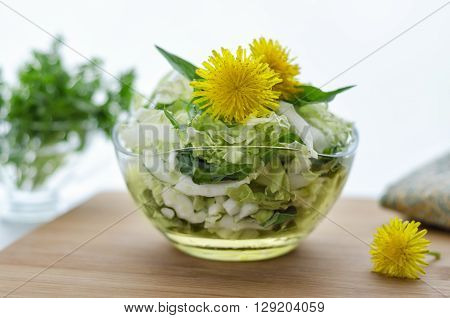 Salad from Chinese cabbage and dandelion leaves, on the table. Morning light, bokeh, decorated with flowers of the dandelion greens in the background and a napkin.