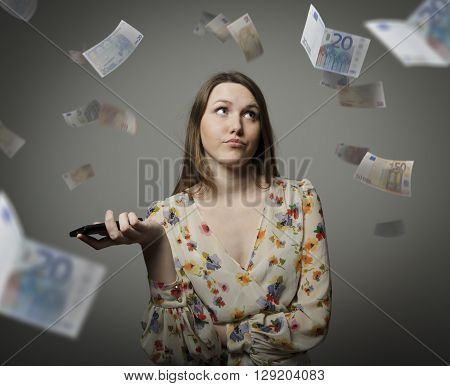 Young woman and falling Euro banknotes. Consumerism concept.