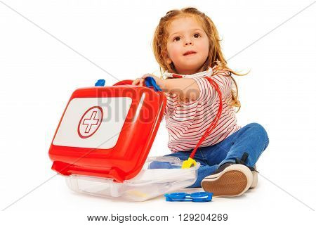 Cute little girl pretending to be a doctor sitting with a toy doctors instruments, isolated on white