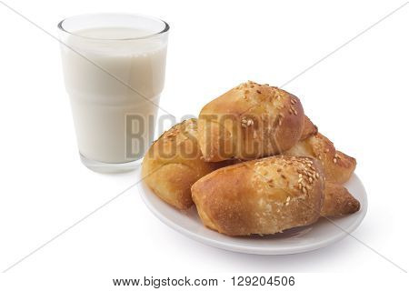 Fresh Serbian pastry rolls with cheese and sesame, on white plate with glass of yogurt, kifla kiflice, isolated on white background