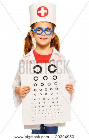 Little girl dressed as ophthalmologist, holding board for sight testing isolated on white background