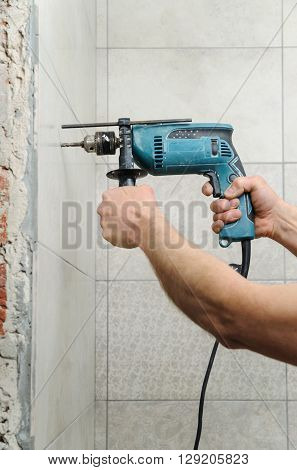 The worker holding a drill and make a hole in the wall.