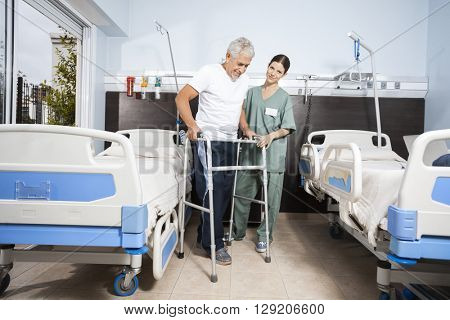 Nurse Assisting Senior Patient In Using Walker At Rehab Center