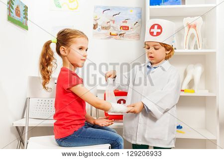 Little boy dressed like a pediatrician doctor bandaging girl's arm with a roller-bandage at the first aid room.