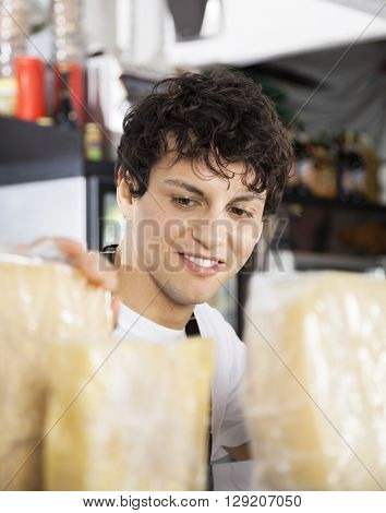 Salesman Arranging Cheese In Shop