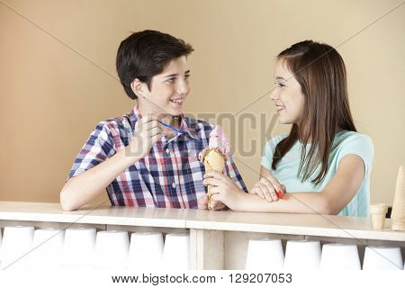 Brother And Sister Having Strawberry Ice Cream In Parlor