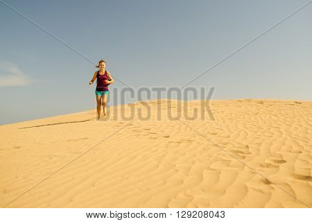 Young woman running on beautiful inspirational desert dunes on sunny summer day. Female runner training and working out jogging and exercising outdoors in nature Gran Canaria Canary Islands Spain.