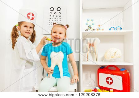 Young pretty girl dressed like a dentist examined her friend at the medical room.
