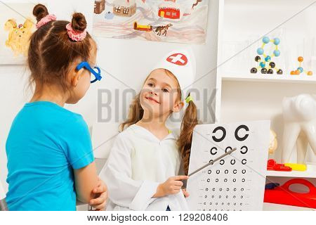 Two girls playing oculist testing patient's sight at medical room.