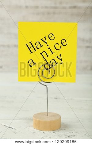 Yellow note paper on a holder on white wooden background