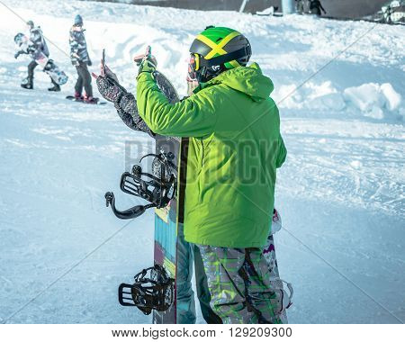 people in ski suits with snowboards taking photo on a hill