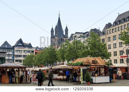 Cologne, Germany - May 16: It is trade fair in Neumarkt square near the church of St. Martin at foggy evening May 16, 2013 in Cologne, Germany.