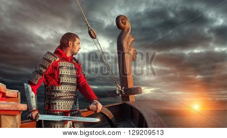 Knight with the sword navigate a warship on the sunset background.