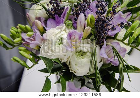 Rich bunch of violet freesia, white buttercup ranunculus peonies, green leaf, lilac lavender, roses, rosemary in bouquet flowers. Summer Background. Rustic style, still life. Holiday wedding floristic. Color tonal effect.