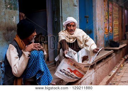 VARANASI, INDIA - JAN 1, 2013: Two aged men discuss the latest news and read the morning newspaper outdoor on January 1, 2013 in Varanasi India. The literacy rate in the Varanasi urban agglomeration is 77 perc.