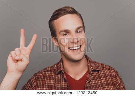 Handsome Cheerful Man Gesturing With Two Fingers