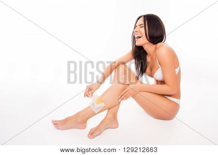 Attractive Woman Shaving Her Leg With Wax Stripe And Feeling Pain