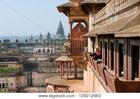 ORCHHA, INDIA - DEC 21, 2012: Woman looking from the balcony of historical Citadel of Jahangir on December 21, 2012. Jahangir Mahal built in 1598. Its high position allowed Cannons to gain superior range.