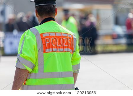 german policeman in vest stands on a street