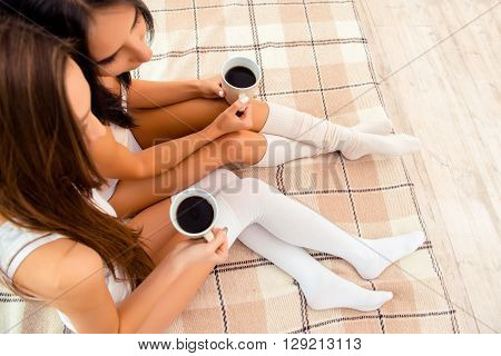 Two Girls On The Bed With Cups Of Coffee In Hands, Top View Point