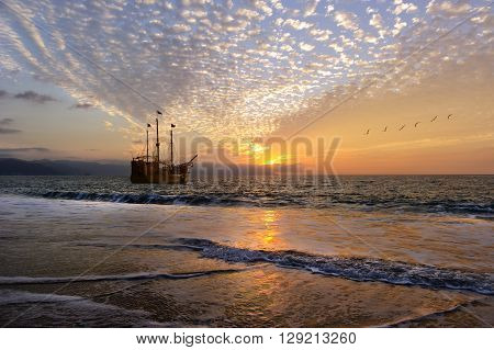 Ship sunset is an old wooden pirate ship with full flags as the sun sets on the ocean horizon in a colorful sunset sky.