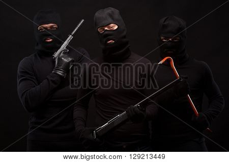Three thieves in balaclavas on their faces, dressed in black. Studio shot on black background. Men holding weapons: guns, rifles, etc. Isolated on black.