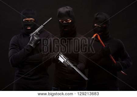 Murders in masks with machine-guns and crowbars over black background. People ae going to atack someone special. Isolated on black.