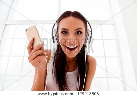 Happy Crazy Girl Listening To Music With  White Headphones And Smartphone