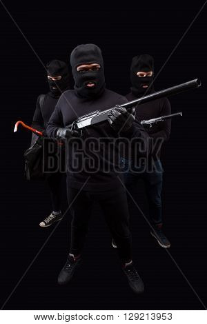 Robbers posing with rifles and crowbars in full length in studio. Robbery, burglary and mafia concepts over black background.  Isolated on black.