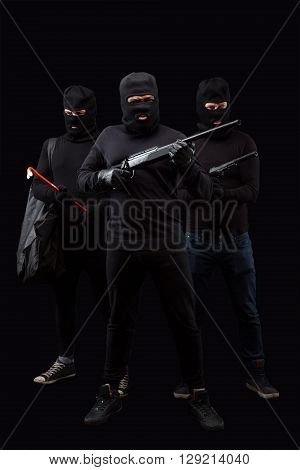 Portrait of dangerous robbers with rifles and crowbars over black background. Men in black balaclavas posing in full length in studio. Isolated on black.