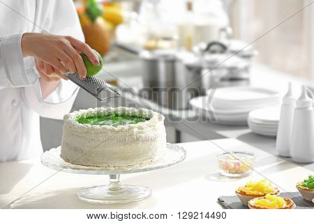 Female hands decorating cake  with lime zest