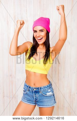 Happy Slim Pretty Woman In Hat Triumphing With Raised Hands