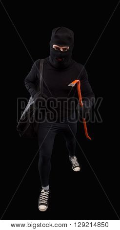 Crime scene - criminal thief or burglar man in balaclava or mask covering face holding crowbar in hand for break opening home door lock. Isolated on black.