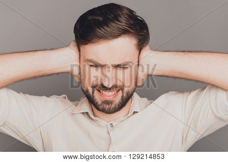 Overworked Sad Man Having Headache And Covering Ears With Hands