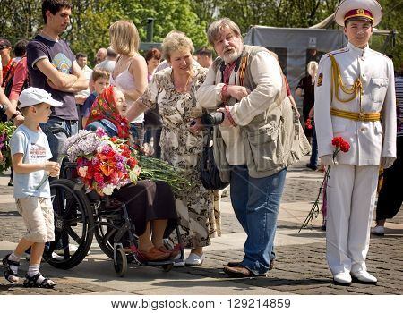 Kyiv, Ukraine - May 8, 2009: Crowd congratulates veteran woman on a wheelchair during Victory Day celebration at the Museum of The History of Ukraine in World War II in Kyiv