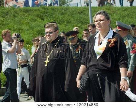 Kyiv, Ukraine - May 8, 2009: Orthodox priest and woman in the crowd during Victory Day celebration at the Museum of The History of Ukraine in World War II in Kyiv