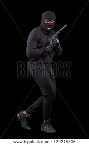 Male thief in mask posing in full length while holding gun pointing up isolated over grey background in studio. Isolated on black.