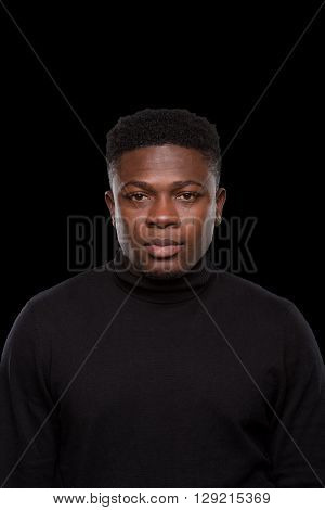 Portrait of dangerous man staying in prison over black background. Black-skinned man looking at camera. Black balaclava. Isolated on black.