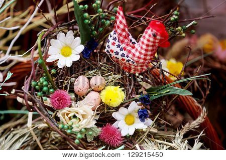 ZAGREB CROATIA - MARCH 26 2016 : A floral arrangement with artificial easter eggs and sewn chicken in Zagreb Croatia.