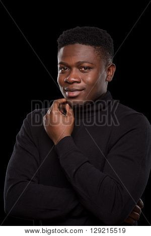 Dangerous robber or burgler smiling for camera while staying in prison over black background. Black-skinned man in balaclava in studio. Isolated on black.
