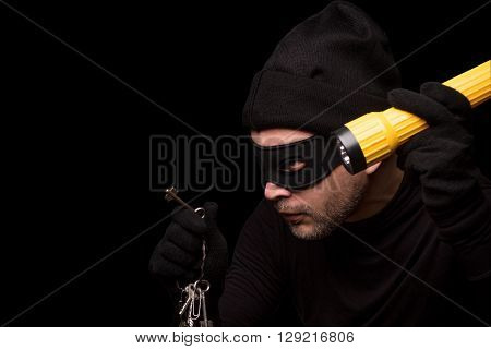 Thief with robbery mask holding flashlight behind over black background. Man in black clothes holding keys from expensive house. Isolated on black.